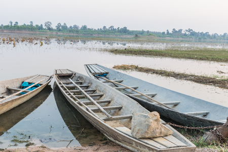 boat of fisherman docking in the riverside in the evening, lotus leaf background and beautiful landscape