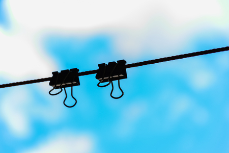 black clips on string or line or rope with blurring blue sky background Stock Photo