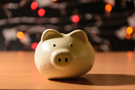a container for saving money in, especially one shaped like a pig, with a slit in the top through which coins are rich,piggy bank on wooden blurring dot color background
