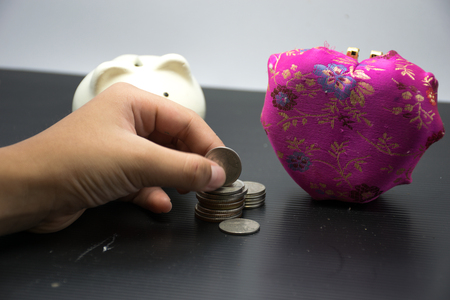 piggy bank and pink heart is isolated ,with hand safe coin for piggy bank,black and white background isolated,piggybank is a container for saving money in, especially one shaped like a pig, with a slit in the top through which coins are dropped Stock Photo