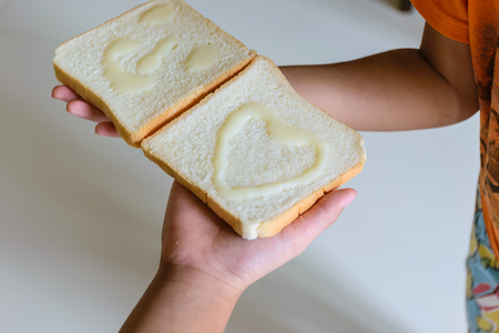 Bread made with condensed milk, will be smile shape and heart shape on face of bread and be  happiness for children eating,two hand holding bread