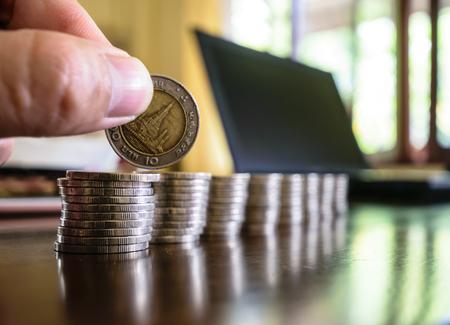 Mains tenant des pièces de monnaie, sont placés sur la table en bois, rangée après rangée de réparations Banque d'images - 84128455