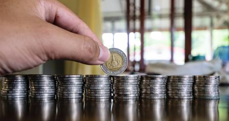 Mains tenant des pièces de monnaie, sont placés sur la table en bois, rangée après rangée de réparations Banque d'images - 84128461