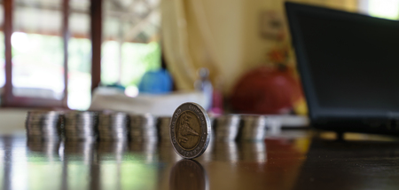 tax aligned: one coin is located on the table and silver coins aligned blurring image background Stock Photo