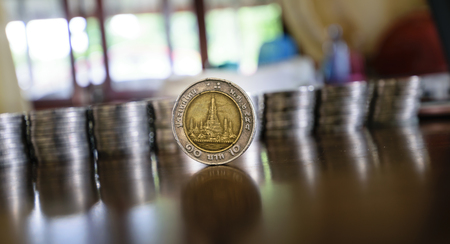tax aligned: There are coins of one study placing it upright on the table beautifully wood in the House. The background is  blurring,concept business image