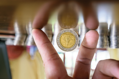 tax aligned: The coins are located between the fingers.There are coins of one study placing it upright on the table beautifully wood in the House. The background is  blurring,concept business image Stock Photo