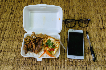 Curry rice, put a foam box placed on the Reed yellow ready to eat and have a mobile phone, glasses and pens. Life for people in a hurry