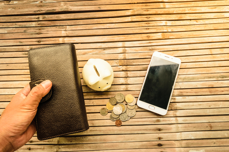 With one hand holding a black leather wallet to bring money to spend buying goods. The backdrop is the old bamboo table represent funds with expenditures. Stock Photo