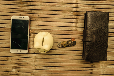 The white pig piggy bank with the money and the phone placed on bamboo table old. Represents a storage saving and creating networks to do business. Reklamní fotografie
