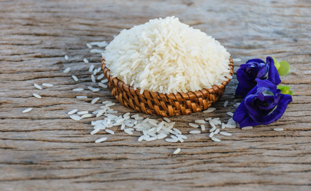 Jasmine rice in wooden basket on old brown wood and flower put inside of rice