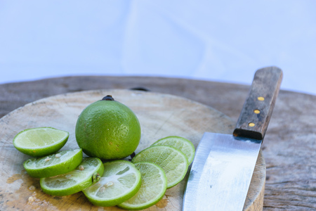 Lime sliced into pieces on a wooden cutting board.