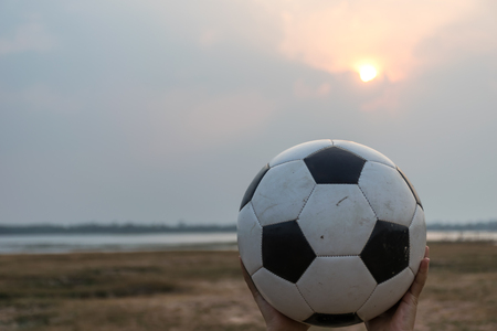 football on sand ground with suset background, classic ground concept, playing funny sport.