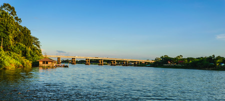 Bridge on river with green mountain and blue sky background, Thailand country concept.