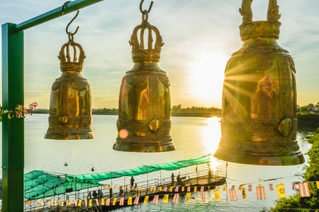 Gold bell in Thailand temple, wallpaper religion, bell with river and sunset background. Zdjęcie Seryjne