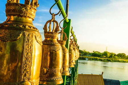 Gold bell in Thailand temple, wallpaper religion, bell with river and sunset background.