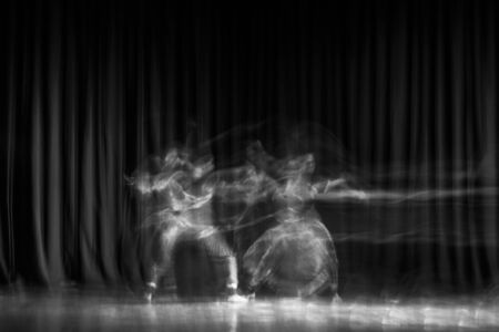 An artistic dancer in a theater shot with a slow shutter speed in order to achieve the desired motion blur.