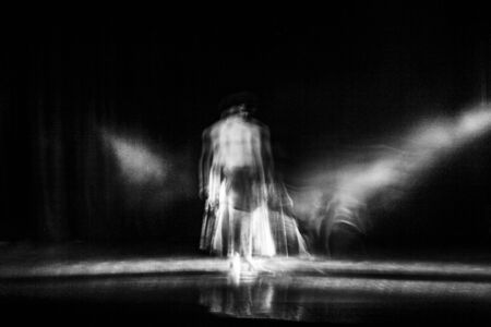 An artistic dancer in a theater shot with a slow shutter speed in order to achieve the desired motion blur. Stock Photo