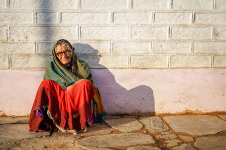 Old aged woman sitting with the support of the wall in the sunset wearing glasses
