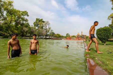 Delhi, New Delhi, India - May 26 2020: Happy Asian kids playing in a lake near India gate in the hot summer. Cheerful and carefree children.