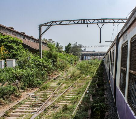 A shot of outside of mumbai local train with railway lines.