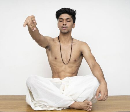 Young indian priest sitting in dhoti, wearing rudraksh, showing up his hand representing giving should be the human nature. Stock Photo - 149099827