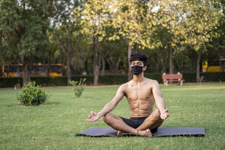 A young indian shredded teenage boy doing yoga aasan in the park on international yoga day