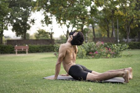 A young indian shredded teenage boy doing yoga aasan in the park on international yoga day, wearing a mask for protection from covid-19 스톡 콘텐츠