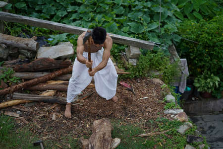 A young boy wearing a white dhoti chopping wood with an axe.