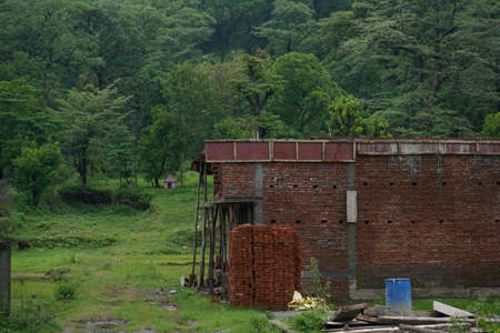 a house being constructed with red bricks in between mountain range.