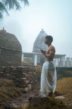 Young man with shredded body wearing dhoti, praying in the temple early in the morning. Standard-Bild