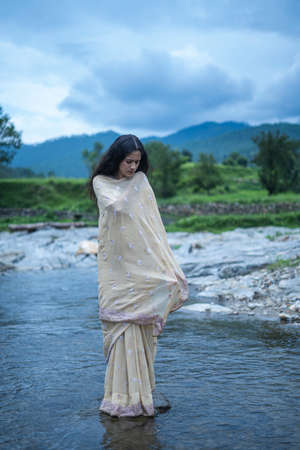 Beautiful Indian young female model wearing traditional saree standing in front of a river landscape with overcast clouds.