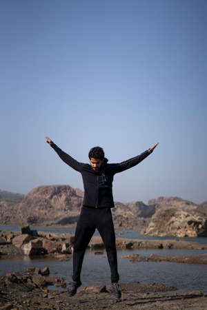 young athletic man doing burpee near a lake surrounded with mountains early in the morning, wearing track suit. Healthy lifestyle concept.