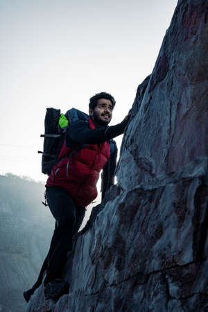 young indian climber and traveler climbing up the mountain rock during sunset. Adventure and sports concept.