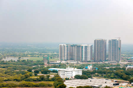 Arial view Cityscape in Gurgaon, Noida, Jaipur, Delhi NCR, Lucknow, Mumbai, Bangalore, Hyderabad showing small houses sky scrapers other commercial real estate infrastructure