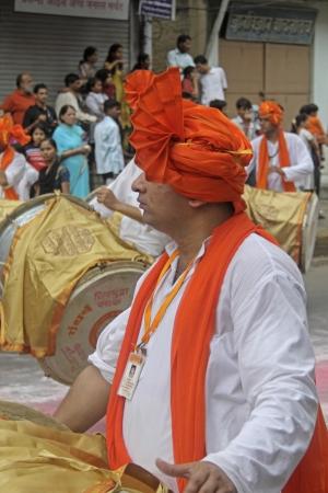 kurta: Indian men wearing headgear called feta and white kurta pajamas and playing musical instrument called