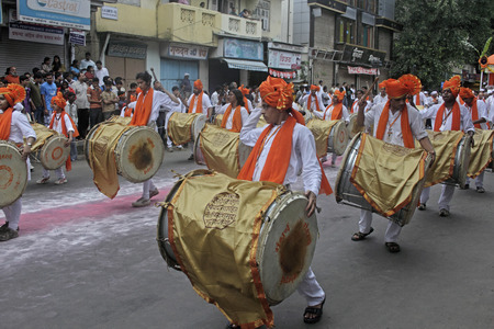 Indian girls   men wearing headgear called feta and white kurta pajamas and playing musical instrument called