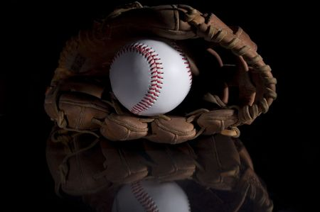 backgrounds: Baseball and baseball glove on black background with refelction in glass. Stock Photo