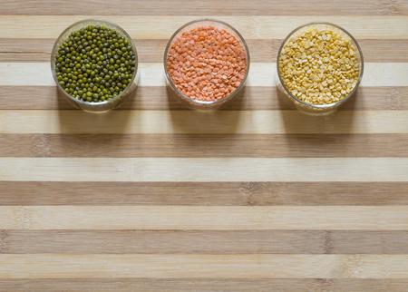 Three bowls of lentils on a chopping board