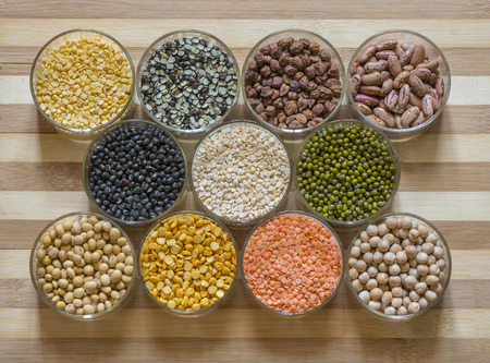 Twelve bowls of lentils and legumes on a chopping board Stock Photo