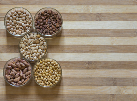5 bowls of legumes on a chopping board