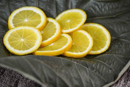 Yellow orange slices on a dried leaf