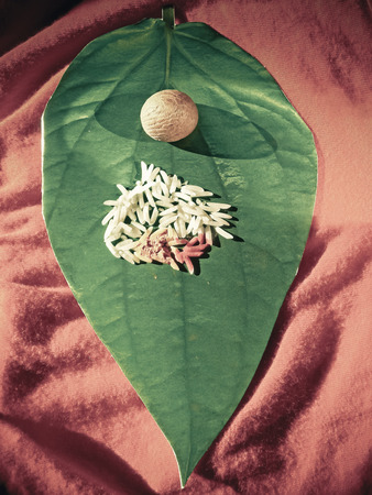 Matrimony card in shape of Betel Leaf, Piper betle with Areca nut, Rice, Kumkum & Turmeric photo