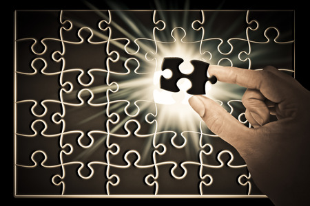 Hands placing last piece of a Puzzle photo