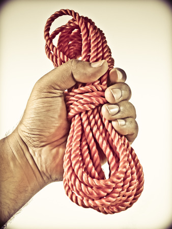 Red nylon heavy duty commercial quality rope in human hand photo