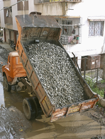 unloading debris from a lorrydumper is going on near a construction site. Pune, Maharashtra, India photo