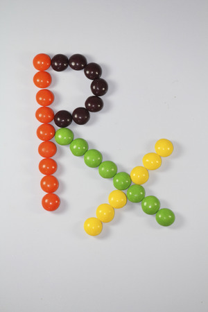Multi-coloured candies arranged in form of Rx Symbol photo