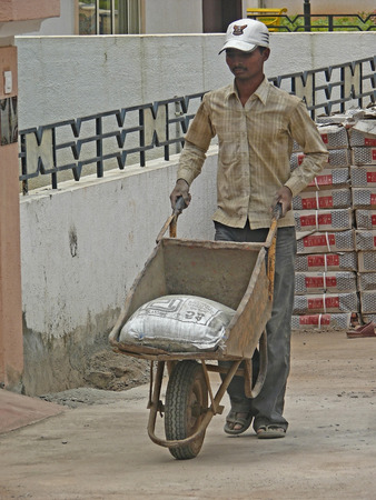 Construction worker moving cement bag in a wheelbarrow, India