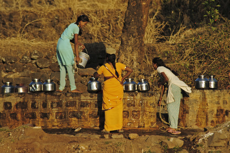Young women fetching water from the local well, Maharashtra, India