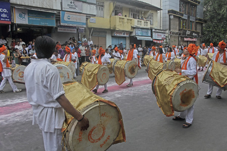 Indian girls & men wearing headgear called feta and white kurta pajamas and playing musical instrument called dhol-taasha during Anant Chaturdashi Ganpati, Visarjan Miravnuk, Pune , Maharashtra , India.