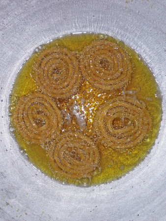 Chakli in hot oil for frying, is the most famous crunchy snack of India photo